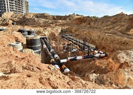 Laying Heating Pipes In Trench At Construction Site. Installing Concrete Sewer Wells And Underground