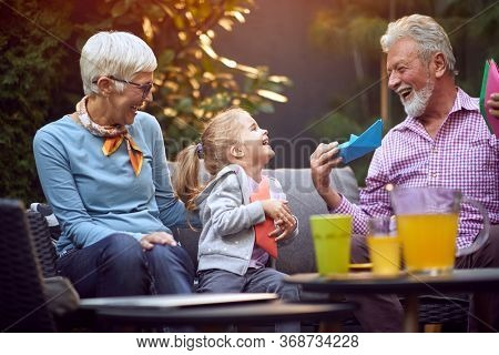 Happy  grandparents enjoying with  granddaughter and playing with paper boat.