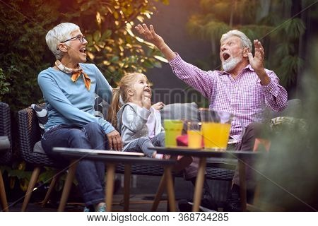 Cheerful granddaughter spending good and funny time with their  happy grandparents.