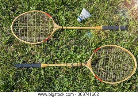 A Set Of Racquets And A Shuttlecock For Playing Badminton Lies On A Green Meadow