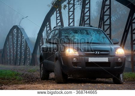 Perechin, Ukraine - Oct 20, 2019: Suv Headlights In Foggy Darkness. Car On The Old Metal Bridge With