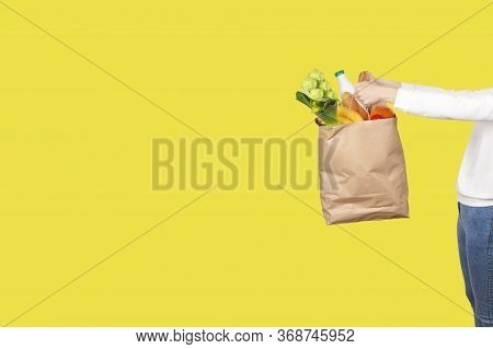 Food delivery or donation concept. Grocery store shopping. Girl holds a paper bag filled with groceries such as fruits, vegetables, milk, yogurt, eggs isolated on yellow.