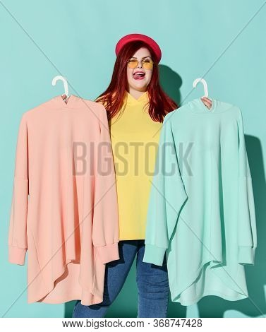 Cheerful Red Haired Plus Size Woman In Casual Yellow Hoodie, Blue Jeans And Pink Hat Chooses Between