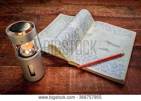 Vintage expedition journal on a picnic table with a candle lantern. Travel log from paddling trip across north eastern Poland in August 1974 - handwriting and drawing in pencil. .