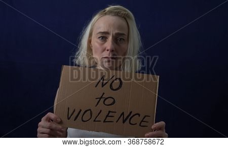 Bruises On The Womans Face. A Woman Holds A Placard With The Text No To Violence.