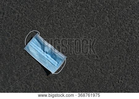 Used Medical Mask On Asphalt. Disposable Face Mask On Pavement With Copy Space. Used Surgical Masks