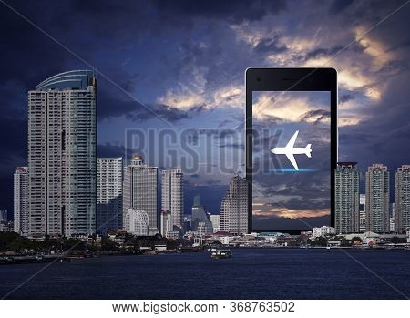 Airplane Flat Icon On Modern Smart Mobile Phone Screen Over Office City Tower, River And Sunset Sky,