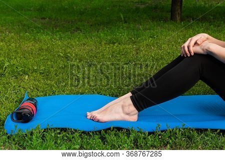 Girl With Bottle Of Water Relax After Exercising Outdoors On Yoga Mat. Legs Of A Girl On A Yoga Mat