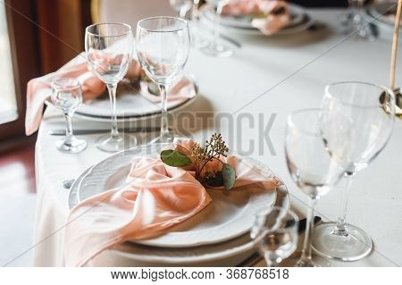 Side View Festive Table Setting With Empty Wine Glasses And Two Plates
