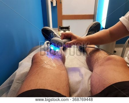Physiotherapist Is Applying Ultrasound Therapy On The Knee Injury With Ultrasound Head Transducer