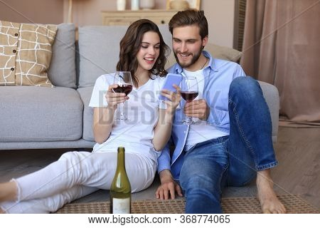 Happy Couple Sitting, Relaxing On Floor In Living Room, Drinking Red Wine. Smiling Young Husband And