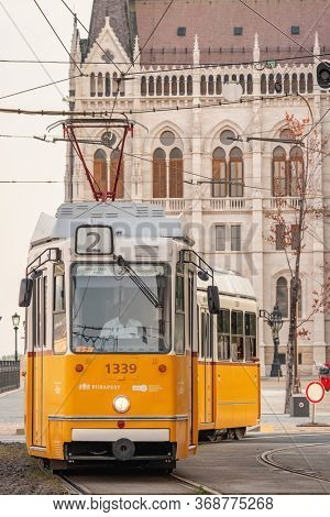 Budapest, Hungary - August 25, 2019: Old yellow tram in front of the Hungarian Parliament Building in Budapest. Public transport in Budapest