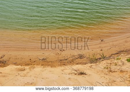 Small Waves On Greenish Water And A Sandy Beach. Beautiful Pond On A Sand Quarry