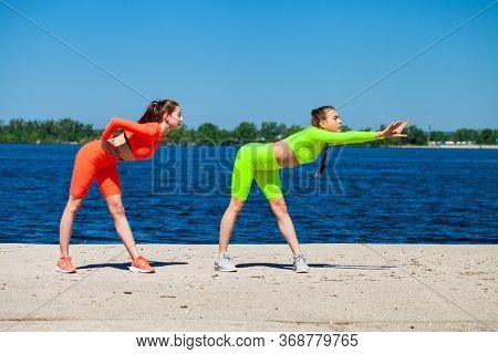 Full body portrait of a young beautiful fitness models in sportswear trains against the blue sky