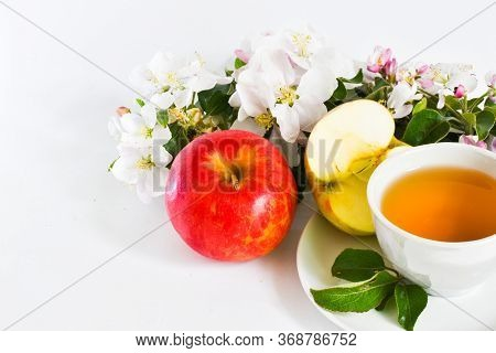 Ripe Red Apples, Flowers Of Apple Trees And A Cup Of Apple Juice And A Sliced apple In Two On A Wh