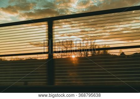Sunset Sky With Clouds Seen Through Fence Lines In Spring.