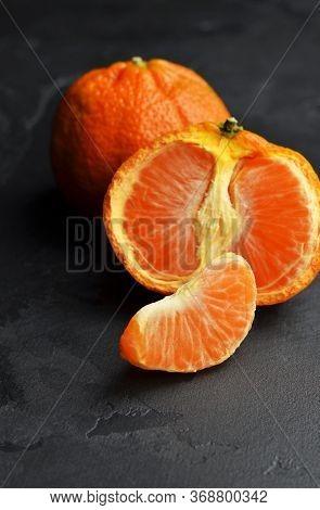 Orange Tangerine Citrus Fruits On Black Background. Tangerine Parts.