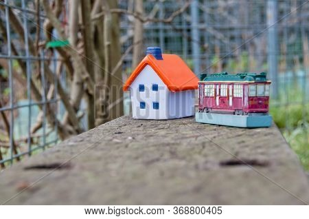 Miniature Soft Toy House On Concrete Fence With A Toy Tram Car