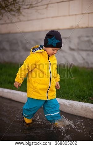 Toddler, White-haired Boy In Puddles In A Protective Suit Against Water And Rubber Boots On Spring P