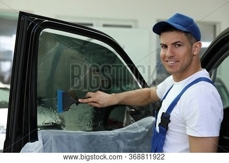 Worker Tinting Car Window With Foil In Workshop