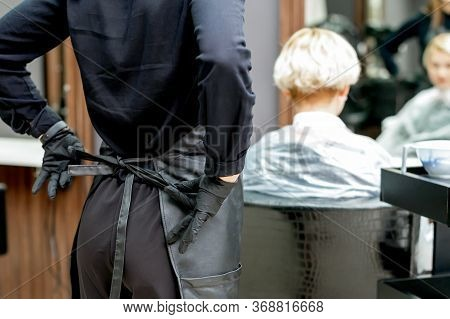 Hairdresser Hands Ties Up Apron In Preparation For A Haircut.