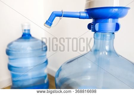 Drinking Clean Water At Home. Close Up Tap View Of Large Blue Pump Cooler Bottle Mechanism For House