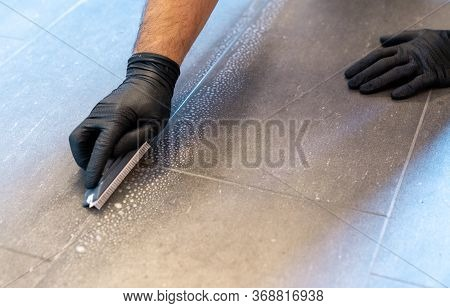 A Close Up Of A Professional Cleaner Cleaning Grout With A Brush Blade And Foamy Soap On A Gray Tile