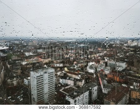 Rain Drops Running Down The Glass Window Overlooking The Whole City Cologne In Germany. Cityscape Vi