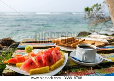 Delicious Breakfast Near The Ocean. Sea Waves In The Background. Romantic Getaway Vacation In Paradi