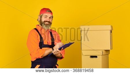Renovation Preparation. Unpacking Moving Boxes. Delivering Packages. Bearded Man Courier Hold Boxes.