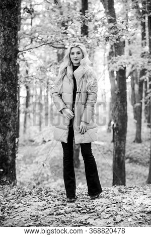 Puffer Fashion Concept. Girl Fashionable Blonde Walk In Autumn Forest. Woman Wear Warm Pink Jacket.
