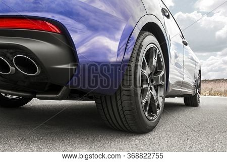 Car On Sky Background. Car Wheels Close Up On A Background Of Asphalt. Car Tires. Car Wheel Close-up