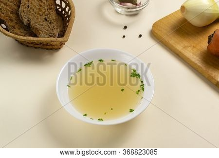 Fresh Bouillon In A White Plate With Herbs And Croutons Of Grain Bread. Hot Soup Made From Meat, Car