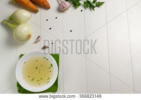 Fresh Bouillon In A White Plate With Finely Chopped Herbs On A Green Napkin With Ingredients On A Wh
