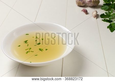 Fresh Bouillon In A White Plate With Finely Chopped Herbs With Parsley And Garlic On A White Backgro