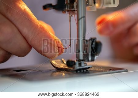 Grandma Fingers Inserting A Red Thread Into A Sewing Machines Needle, Close-up