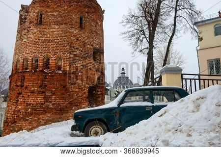 An Old Passenger Car Stands In A Snowdrift Near The Old Fortress Tower