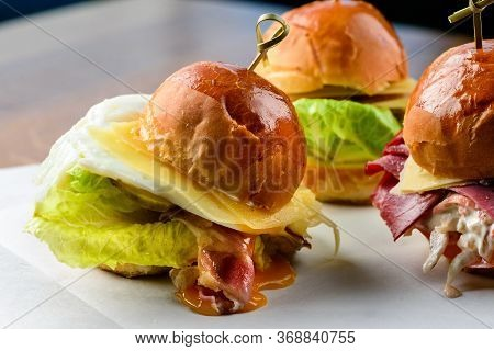 Close Up Mini Burger. Delicious Hamburger With Fried Eggs, Cheese And Bread On A Wooden Table. Ameri