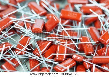 Close-up Of A Bunch Of Red Capacitors Lies On Top Of Each Other At An Office Equipment And Computer