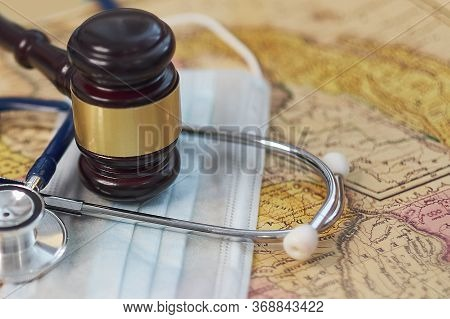Brown Gavel And A Medical Stethoscope And A Protective Mask On A Geographical Map. Symbol Photo For