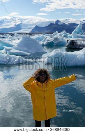 Enjoying Icelandic Nature. Excited Female Tourist In Yellow Jacket Visiting Jokulsarlon Glacier Lago