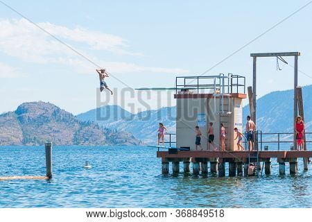 Peachland, British Columbia/canada - August 6, 2017: A Boy Leaps Of The Dock Into Okanagan Lake At S