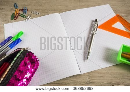 School Supplies Lie On A Wooden Table. Stationery Is Scattered Around The Table.