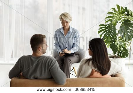 Family Psychotherapy. Professional Marital Therapist Taking Notes Talking With Couple During Appoint