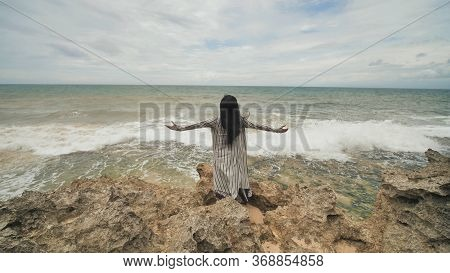 Indonesian Girl Enjoys Life With Outstretched Hands On The Rocky Shore On The Island Of Bali.