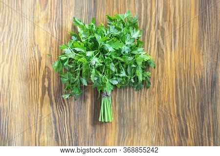 Bunch Of Green Parsley In Center Of Brown Textured Wooden Background. Horizontal With Copy Space. Fr