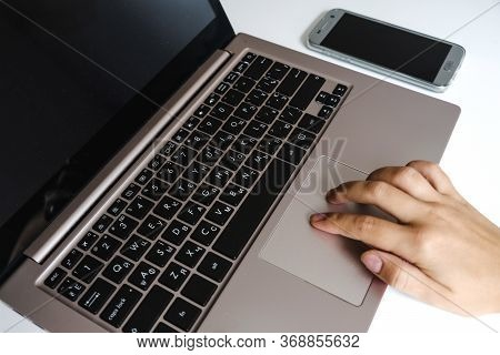 Two White Female Fingers Using Laptop Touchpad Gesture. Modern Home Office Workspace. Using Computer