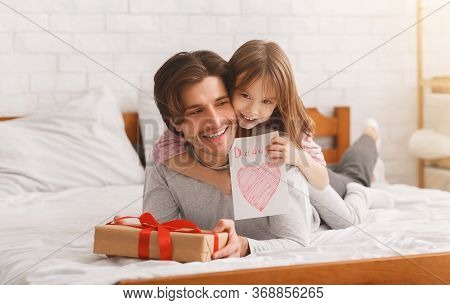 Lovely Preschool Girl Greeting Her Happy Daddy With Father Day, Giving Him Gift Box And Greeting Car