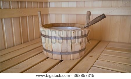 Wooden Dishes In The Sauna. Brooms With Dried Herbs In A Wooden Bath. Relaxation Concept.