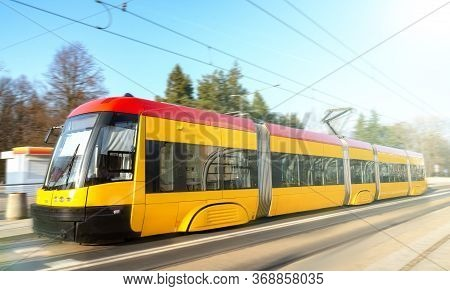 Modern Urban Rail Transport. Yellow Tram With Motion Blur Effect Moves Fast In The City. High Speed